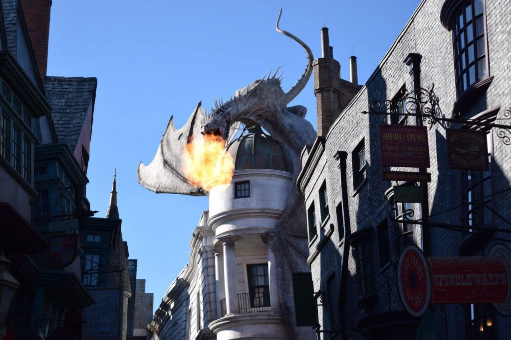 At the Escape from Gringotts ride at Universal Orlando Resort, a dragon breaths fire over the heads of guests.
